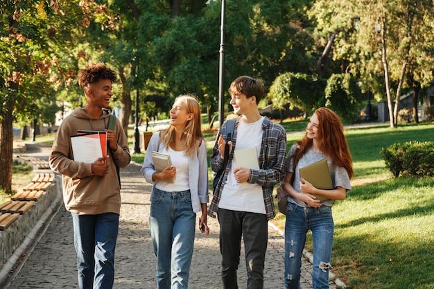 Jovens estudantes multiétnicos rapazes e raparigas sorrindo enquanto caminham juntos no parque com livros