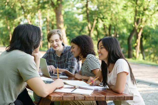 Jovens estudantes sorridentes sentado e estudando ao ar livre