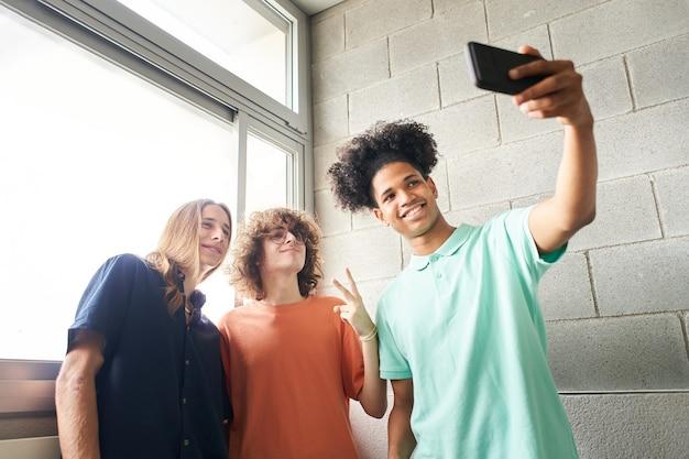Jovens estudantes tirando uma selfie na escola e se divertindo juntos com jovens muito diferentes