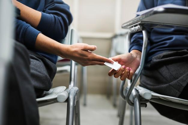 Jovens estudantes traindo um exame