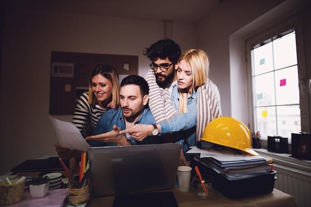Jovens executivos cansados que procuram a solução de problemas enquanto permanecem após o horário normal de trabalho.