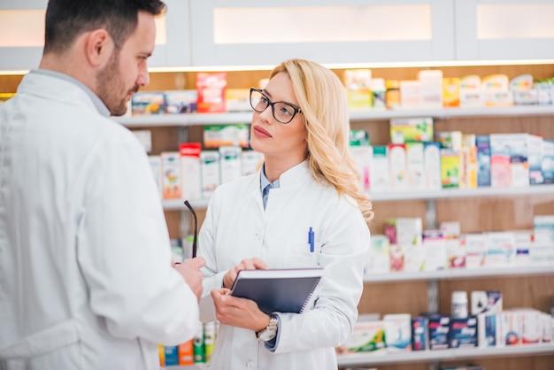 Jovens farmacêuticos discutindo no trabalho.