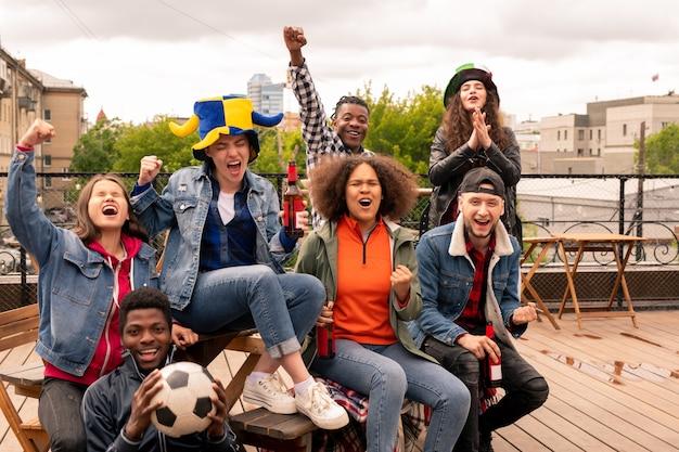 Jovens fãs urbanos expressando alegria e torcendo por seu time de futebol enquanto assistem à transmissão no telhado
