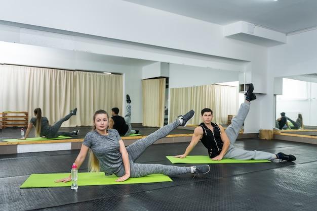 Jovens fazendo exercícios na academia juntos