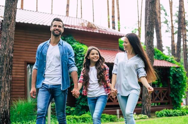 Jovens felizes e modernos pais com uma linda filha caminhando ao ar livre
