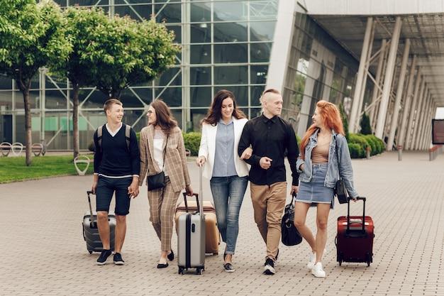 Jovens felizes e positivos com bagagem ao ar livre perto do aeroporto