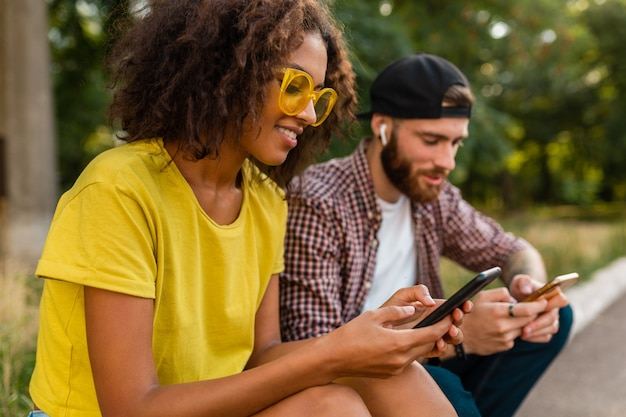 Jovens felizes e sorridentes amigos sentados no parque usando smartphones, um homem e uma mulher se divertindo juntos