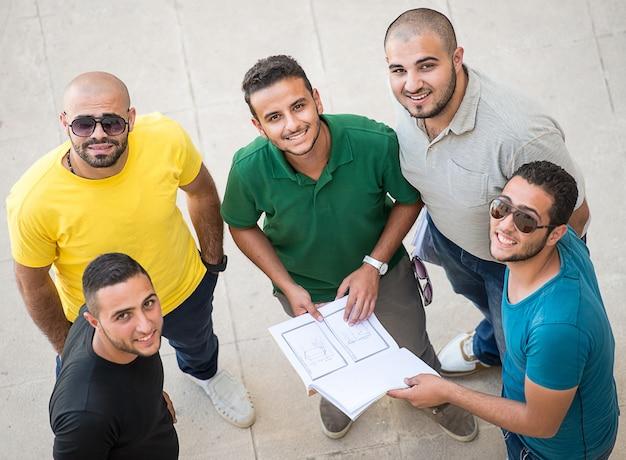 Jovens felizes em pé e conversando juntos no campus universitário