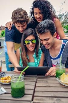 Jovens felizes procurando tablet eletrônico, sentados ao redor da mesa com bebidas saudáveis em um dia de verão ao ar livre. conceito de estilo de vida dos jovens.