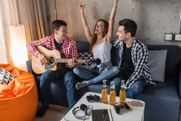 Jovens felizes se divertindo, festa de amigos em casa, companhia hipster juntos, dois homens uma mulher, tocando violão, sorrindo, positivo, relaxado, bebendo cerveja