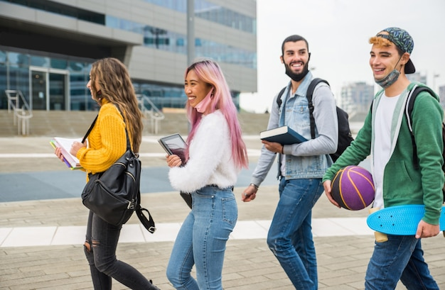 Jovens felizes se encontrando ao ar livre e usando máscaras durante a pandemia covid-19