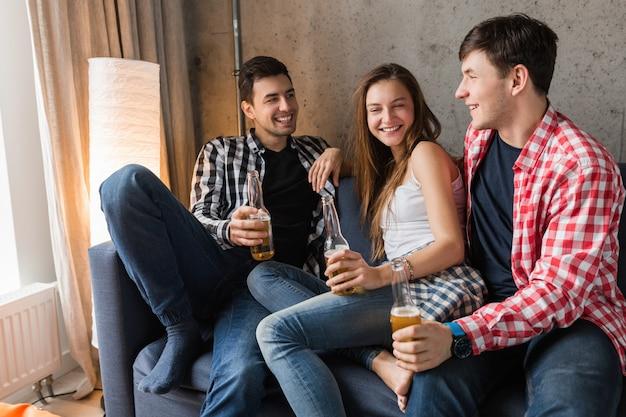 Jovens felizes sentados no sofá, bebendo cerveja, fechando as mãos brindando, se divertindo, festa em casa de amigos, companhia hipster juntos, dois homens uma mulher, sorrindo, positivo, relaxado, passear, rindo