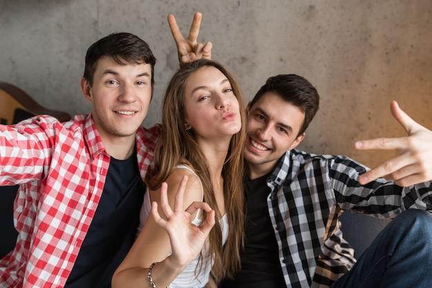 Jovens felizes tirando fotos engraçadas de selfie, sentados no sofá