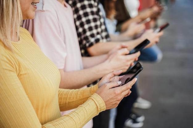 Jovens felizes usando telefones celulares ao ar livre - foco na garota da esquerda