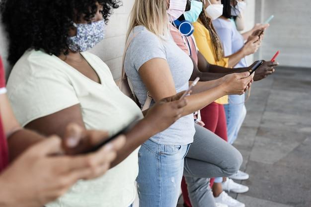 Jovens felizes usando telefones celulares enquanto usavam máscaras de segurança ao ar livre - concentre-se na garota do centro