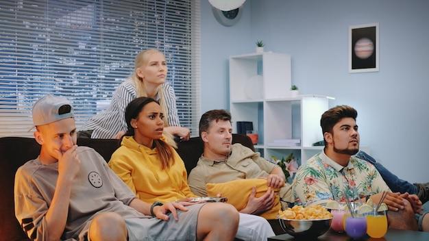Jovens ficando tristes com a sua equipe de esporte assistiram na tv