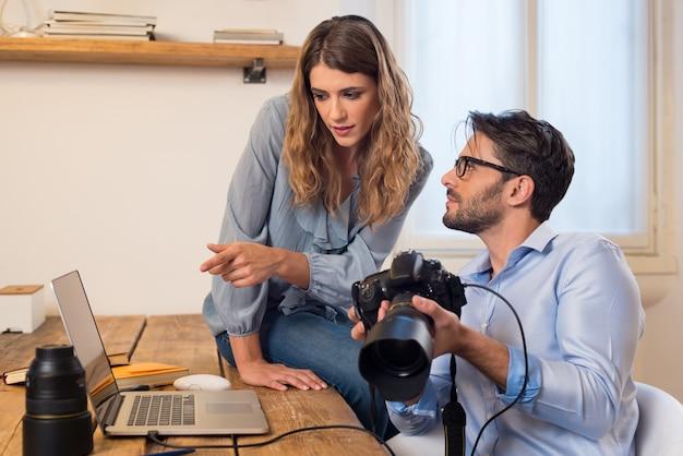 Jovens fotógrafos olhando fotos no laptop. fotógrafo assistente ajudando fotógrafo na seleção das fotos. jovem equipe de fotógrafo trabalhando em um estúdio profissional.