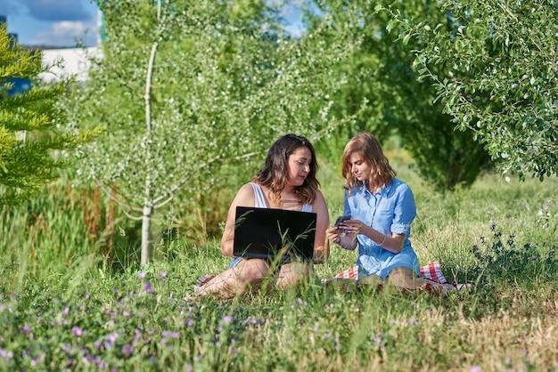 Jovens freelancers trabalhando ao ar livre em um parque em uma tarde ensolarada de verão