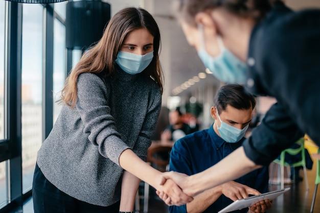 Jovens funcionários com máscaras protetoras apertando as mãos uns dos outros