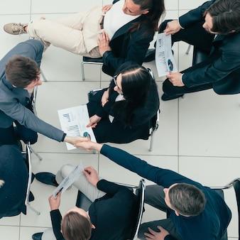 Jovens funcionários se apoiando mutuamente com um aperto de mão