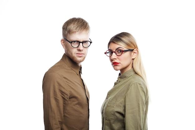 Jovens funcionários sérios do sexo masculino e feminino usando óculos e olhando com expressões concentradas ou irritadas posando