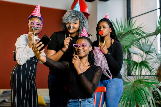 Jovens garotas afro-americanas bonitas comemoram aniversário e fazem um selfii em seu smartphone.