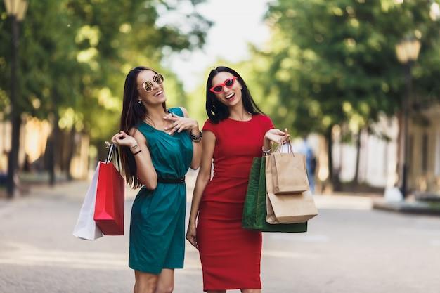 Jovens garotas atraentes com sacos de compras na cidade de verão. mulheres bonitas em óculos de sol e sorrindo. emoções positivas e o conceito de dia de compras.