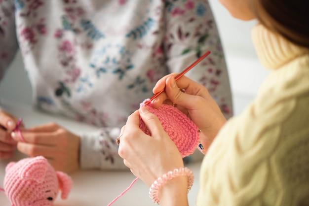 Jovens garotas atraentes em uma aula de tricô