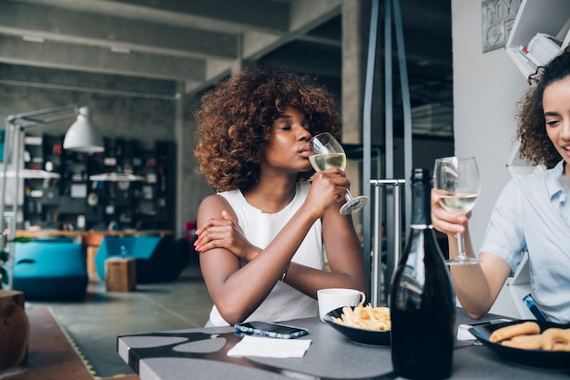 Jovens garotas bebendo e sentado no bar