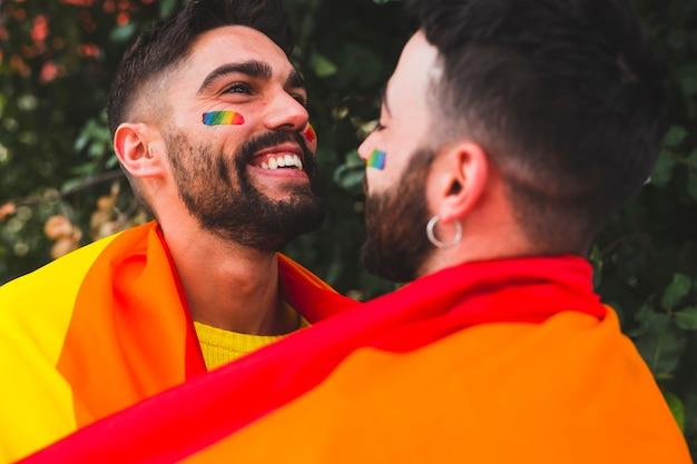 Jovens gays sorrindo e abraçando na rua