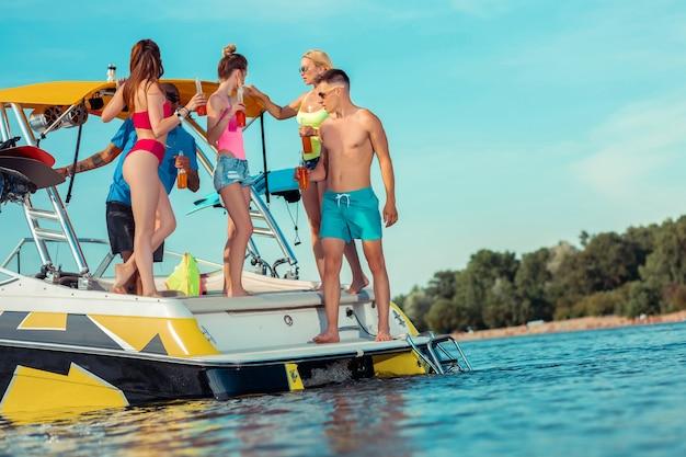Jovens. grupo de jovens com garrafas nas mãos, em um barco de recreio, olhando para longe