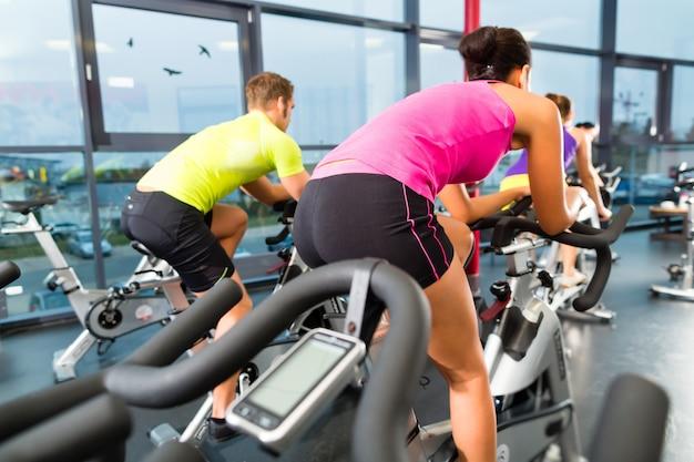 Jovens - grupo de mulheres e homens - fazendo esporte girando no ginásio para aptidão