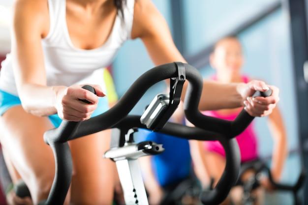 Jovens, grupo de mulheres e homens fazendo esporte girando no ginásio para fitness