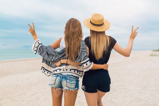 Jovens hippie mulheres bonitas de férias em uma praia tropical, roupa de verão elegante, feliz, tendência da moda, estilo hippie, acessórios da moda, amigas juntas, humor positivo, vista de trás