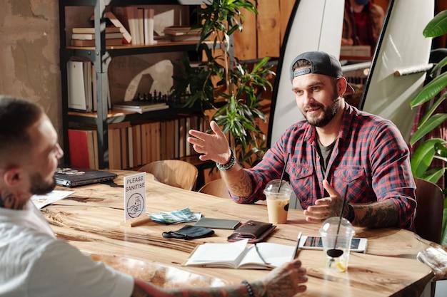 Jovens hipster sentados à mesa em um café com design exclusivo e discutindo planos e ideias