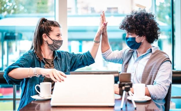 Jovens influenciadores milenares em espaço de coworking com máscara