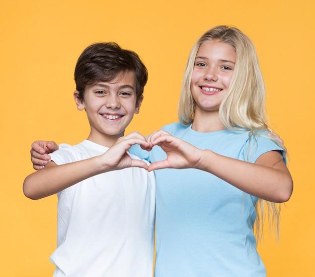 Jovens irmãos fazendo formato de coração com as mãos