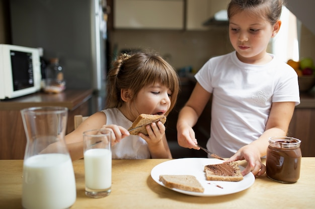 Jovens irmãos tomando café da manhã em casa