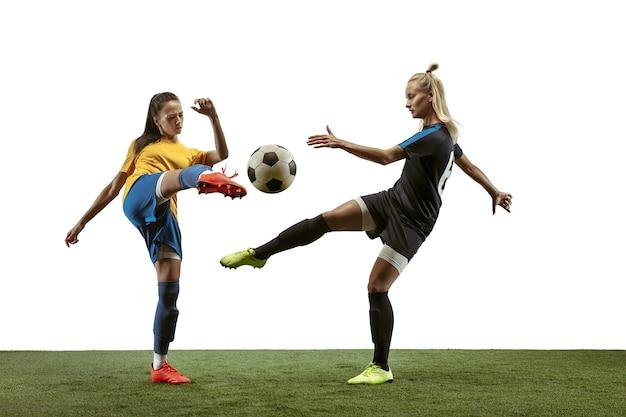 Jovens jogadoras de futebol ou futebol feminino com cabelo comprido em roupas esportivas e botas de treinamento em fundo branco. conceito de estilo de vida saudável, esporte profissional, movimento, movimento. lute pelo gol.