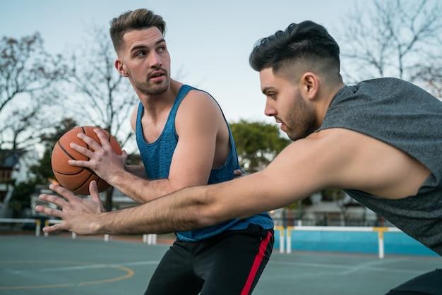Jovens jogadores de basquete jogando um contra um na quadra ao ar livre. conceito de esporte e basquete.
