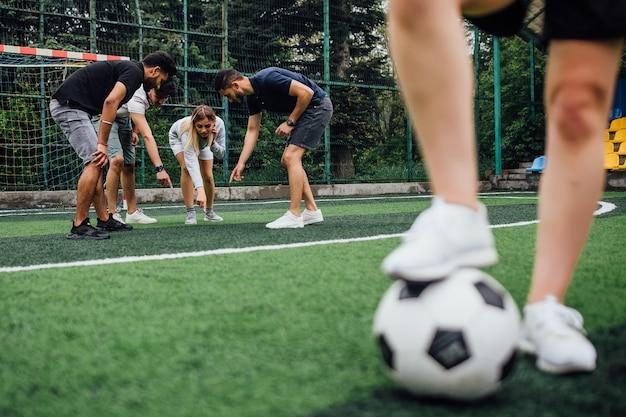 Jovens jogadores de futebol com a bola em ação ao ar livre
