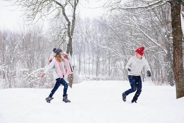 Jovens jogam bolas de neve na floresta de inverno