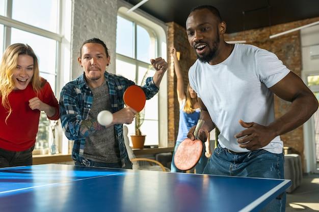 Jovens jogando tênis de mesa no local de trabalho se divertindo