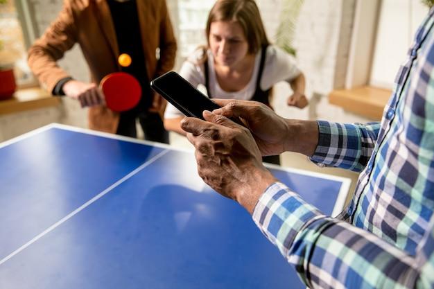 Jovens jogando tênis de mesa no local de trabalho, se divertindo