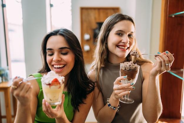 Jovens latinas sentadas em um café