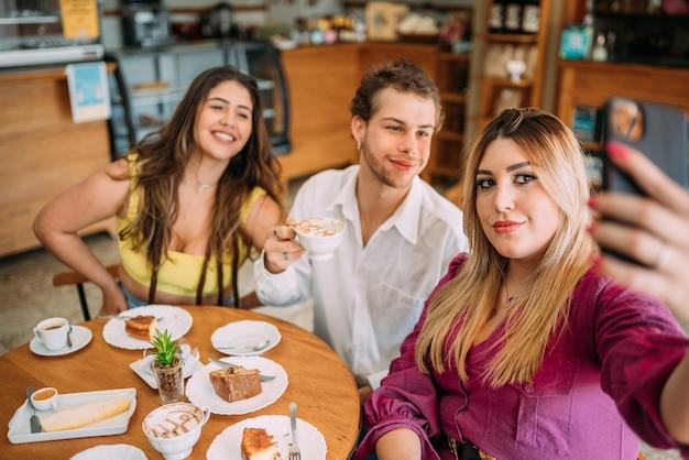 Jovens latinos sentados em um café tirando uma selfie com o smartphone