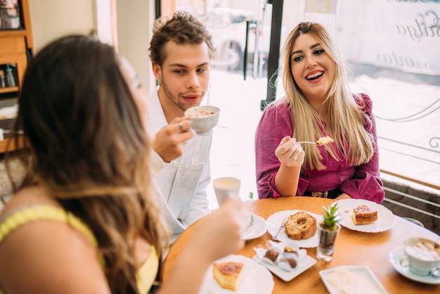 Jovens latinos sentados em um café tomando café com bolos e ouvindo histórias de vida engraçadas