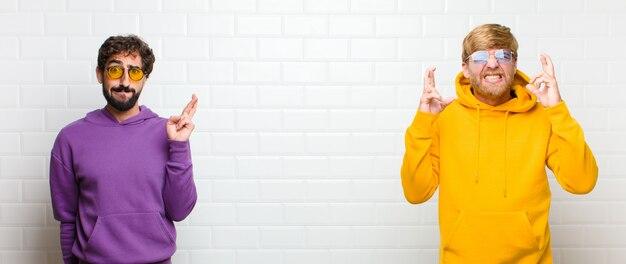 Jovens legais, sentindo-se nervosos e esperançosos, cruzando os dedos, rezando e esperando boa sorte contra a parede de azulejos brancos