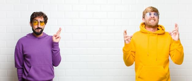 Jovens legais, sorrindo e cruzando ansiosamente os dois dedos, sentindo-se preocupados e desejando ou esperando boa sorte sobre a parede de azulejos brancos