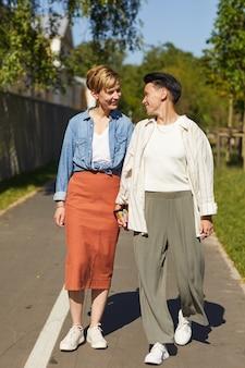 Jovens lésbicas felizes de mãos dadas e sorrindo umas para as outras enquanto caminhavam ao longo da estrada no parque